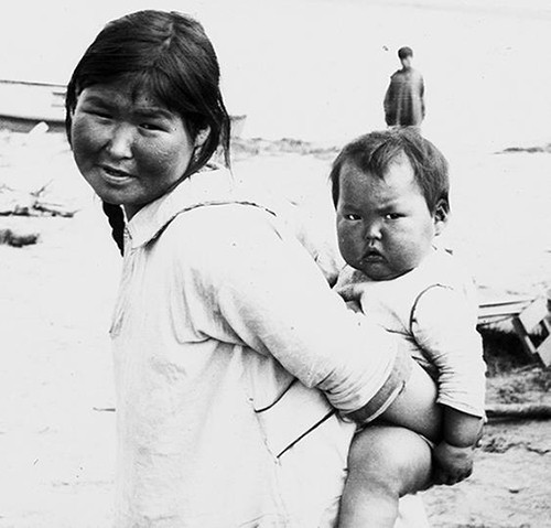 A photo of an Eskimo woman with her baby