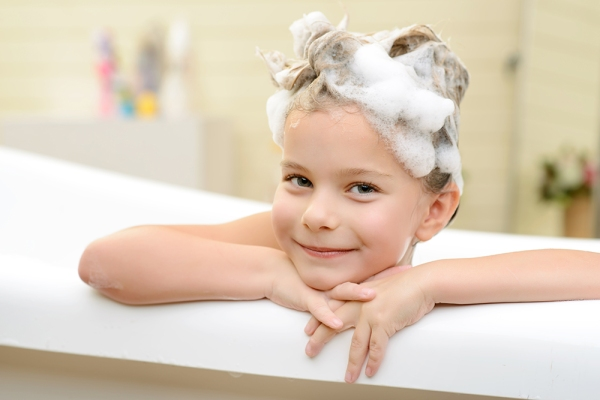 Happy kid. Pleasant little girl folding her hands and leaning on them while taking bath