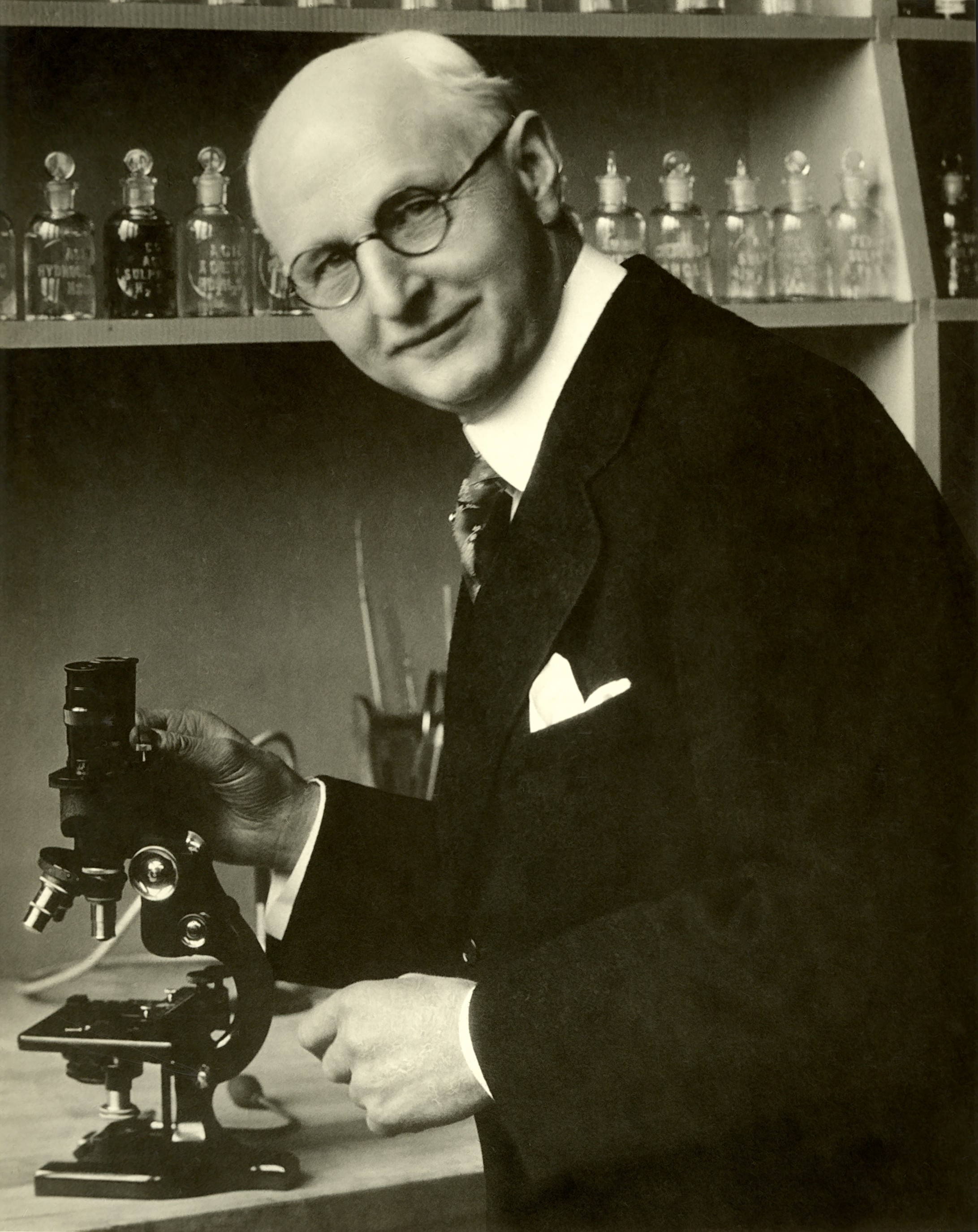 Dr. Weston A. Price with his hand on a microscope
