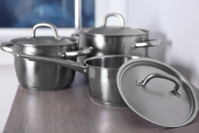 Kitchenware concept. Stainless saucepans on kitchen table